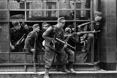 German soldiers of the 36th Waffen Grenadier Division of the SS (SS-Sturmbrigade Dirlewanger) do battle from the window of a townhouse at Focha 9 Street with Polish insurgents during the Warsaw Uprising. Warsaw, Poland. August 1944.