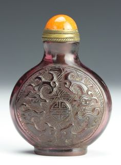 China, 19th C., purple Peking glass snuff bottle of a circular form with auspicious symbols and decorative carvings. Height 2 3/8 in.