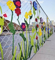 This is a cool way to make a chain-link fence cheerful! Yarnbombing crochet art from Ladies Fancywork Society 3d Street Art, Fence Weaving, Guerilla Knitting, Fence Art, Group Art, Yarn Bombing, Collaborative Art, Crochet Art, Outdoor Art