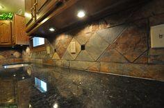 Slate Tile Backsplash With Uba Tuba Granite Countertops