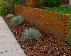 In Love with a House | We got ourselves some affordable curb appeal with a modern-style fence, blue wheat grass plants, and bark mulch. Take a peek at the blog post!