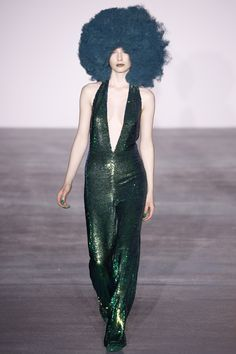 This look comes from the Ashish fall 2016 ready to wear show and draws historical inspiration from 1970's disco clothing. The model is wearing an exaggerated v-neck jumpsuit in a shimmery green material. She also has on a large afro wig which was a popular hairstyle for the time period. 2/22/16
