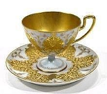 Porcelain cabinet cup and saucer with gilt and jewelled decoration onto an egg blue ground with gilded interior