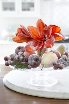 Sugared Amaryllis and fruit centerpiece - Lightly brush egg whites mix ever so gently upon fruit and flowers blooms. Sprinkle super-fine sugar partially on both fruit and flower. Place upon cake plate with some greens!