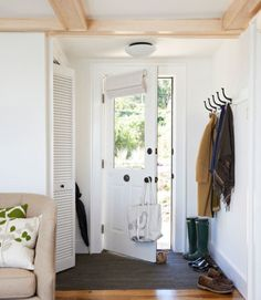 The owners of this renovated 1950s fishing shack closed off an extra door (originally to the right of the front door) to make extra wall space to hang jackets, bags and hats. To protect the wooden floors from wet, muddy feet, the owners added a layer of recycled tire flooring just inside the front door.