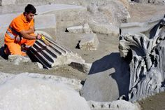 A worker searches a site along the Via Flaminia in northern Rome where a mausoleum was found and believed to be the tomb of Marcus Nonius Macrinus, a general and statesman in the late second century AD, Oct. 21, 2008.