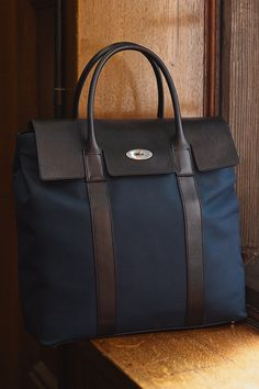Shop the Tall Bayswater at Mulberry.com.  A smart and spacious day bag, featuring our iconic Postman's Lock to secure your belongings. Available in a selection of classic leathers or a lightweight combination of nylon and leather.
