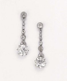 A PAIR OF BELLE EPOQUE DIAMOND PENDANT EARRINGS  Each designed as a circular-cut diamond with foliate surmount suspended from the diamond collet line, mounted in platinum and gold, circa 1910, 3.5 cm. long