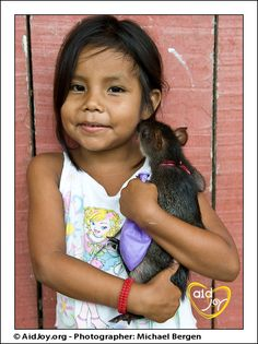 An adorable little girl and her pet Agouti in the Amazon Rainforest.