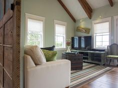The home's second-floor relaxation and gathering space offers the high-tech features of a home theater, plus concealed sleeping space for overnight guests.