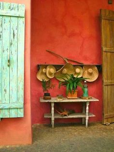 The classic tones of Mexico are showcased on this rust painted wall with a timber barn-style doors contrasting in a wash-out celadon. The interesting decorative touch is the playful row of straw hats arranged above a small outdoor console. Mexican Interior Design, Mexican Designs, Interior And Exterior, Exterior Design, Mexican Hacienda, Hacienda Style, Mexican Colors, Mexican Style, Wall Colors