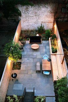 terrasse de jardin moderne, dallage en pierre grise, fauteuils design en bleu et table en bois