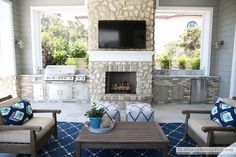 Chic covered patio features Restoration Hardware Leagrave Classic Lounge Chairs and Sofa lined with blue and turquoise ikat pillows facing a Leagrave Coffee Table atop a Dash & Albert rug.
