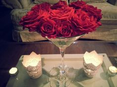 Decorative over sized martini glass used to hold fresh cut red roses paired with lace cut out metal candle holders from IKEA... makes for a beautiful living room center piece