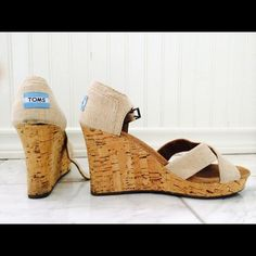 """TOMS cork wedge sandal These are gently used TOMS wedges purchased this past summer. Burlap straps crisscross over open toe. 3 1/2"""" cork wedge and 3/4"""" platform. Very comfortable. Size 8. As documented in the picture, a small piece of cork has flaked off of one of the wedges leaving a bit of black to poke through. The heel is not coming apart from the sole. TOMS Shoes Wedges"""