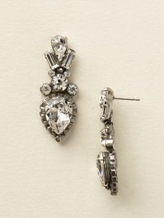 Curb Chain Accented Pear Crystal Statement Earrings in Clear Crystal. A large central pear crystal outlined with curb chain dangles from a cluster of round crystals. Topped with a ray created by two baguette stones on either side of a smaller pear shaped crystal, these exotic baubles will stun and amaze! These beautiful earrings and other beautiful artisan fashion earrings are available online at sorrelli.com.