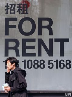 A Chinese man smokes outside a business center with offices available to rent in downtown Beijing on March 17, 2017. China's property…