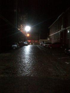Floodlit cobbled street on a rainy night.