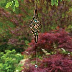 "Wind Spinner, Item #42975, $10.99.  Watch this kinetic copper-finished wind sculpture as it gracefully spins in the wind. The twisted cage holds 3 iridescent marbles with 1 additional marble that swings from the metal chain for a stunning visual effect. 14"" long, ready to hang."