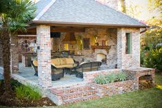 outdoor kitchen/living space (side view).  Brick, slate floor, bahama shutters, lantern, planter...