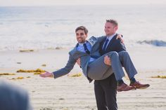 Groom being carried by his best man at his beach wedding.