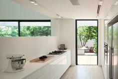 בין הסלון למטבח מפריד קיר שבו פתח מוארך. ארונות המטבח נבנו לאורך שני קירות מקבילים, שביניהם דלת יציאה לחצר (צילום: עמית גרון)