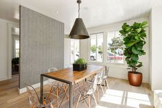 Designer wallpaper and a contemporary pendant light accent the light-filled dining area.