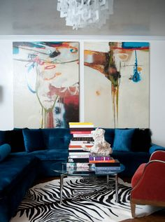 source: Smith Boyd Interiors      Glamorous living room with indigo blue velvet sectional sofa and modern chrome and glass cocktail table over zebra cowhide rug. Two large abstract pieces of art hung above sofa and silver leaf ceiling with contemporary light fixture.