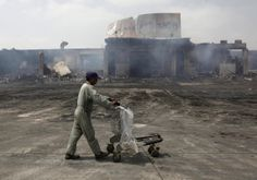 A man pushes a trolley past a damaged building on the tarmac of Jinnah International Airport, a day after Sunday's attack by Taliban militants, in Karachi June 10, 2014. Taliban militants disguised as security forces stormed into Pakistan's busiest airport on Sunday night, triggering an all-night battle in which at least 27 people were killed.