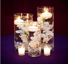 Centerpieces: silk flowers in distilled water with floating candles and colored/colorless rocks