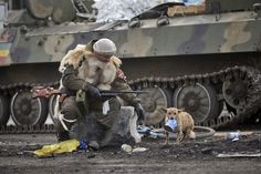 A Russian-backed rebel, his feet on Ukraine's flag, watches a small dog holding a can of food in its mouth in Debaltseve, Ukraine, on February 20, 2015.
