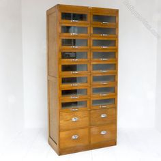 A mid 20th century haberdashery cabinet, double banked and made from solid and veneered oak.