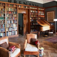 This traditional home office with fitted bookcases, leather chairs and a piano has a classic library look.
