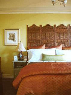 An ornate wooden room screen makes a perfect exotic headboard.  eclectic bedroom by ADEENI DESIGN GROUP