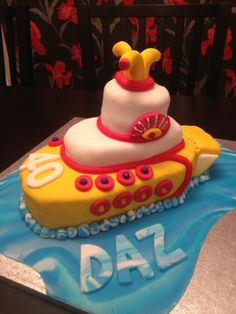 """Beatles inspired yellow submarine cake. Use crock-pot for base, blue crock for middle and cupcake for top, loaf pan for """"tail"""". Use regular icing decorate with candy, twizlers, red and white bendy straws (the paper straws from Wegmans?) Blue Jello around base?"""