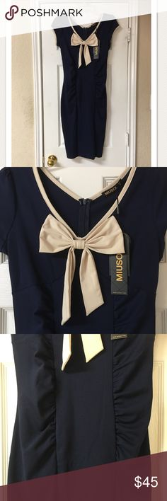 """NWT! Miusol Navy Body Con Dress with Ivory Bow NWT! Miusol Navy Body Con Dress with Ivory Bow. Absolutely adorable! Great condition! Ruching down the body. So figure flattering. Rayon/Polyester/Spandex Blend. Bust 34"""", length 40"""". Miusol Dresses Midi"""