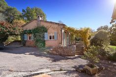 Julia Child's House For Sale in the South of France—Climbing greenery and light blue shutters punctuate the peachy stucco exterior.