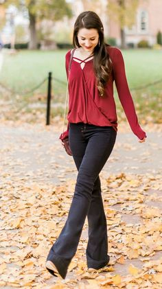 Comfy and casual Thanksgiving outfit idea | Burguny surplice top with dark wash flare jeans, cognac boots, gold Kendra Scott Sophee earrings, and Vera Bradley Carson Mini Saddle Bag | What to wear out on Thanksgiving Eve by fashion blogger Stephanie Ziajka from Diary of a Debutante
