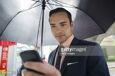 Stock Photo : Businessman texting with cell phone under umbrella