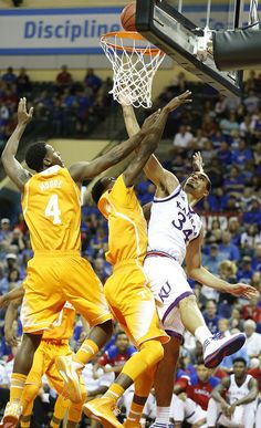 Kansas forward Perry Ellis (34) gets a bucket and a foul from Tennessee forward Willie Carmichael III, center during the second half on Friday, Nov. 28, 2014 at the HP Field House in Kissimmee, Florida. At left is Tennessee forward Armani Moore (4). #KU
