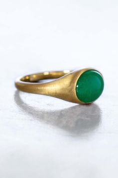 A smooth and plump lively green cabochon (polished but unfaceted) sits at the center of this glowing recycled raw finished 18k gold signet ring. Low profile and securely bezel set this ring is easy to wear. Imagined as a self-purchase or truly unique engagement band this ring can be worn on any finger you would like. As with all S. Kind & Co. rings, sizing is complimentary before shipment (takes about 7 days).