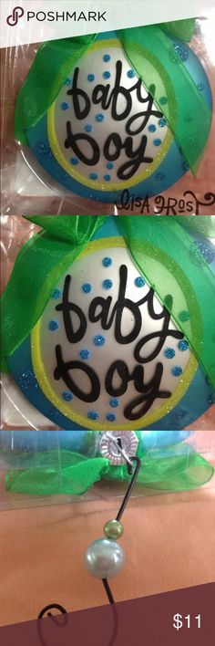 "Lisa Frost ""Baby Boy"" hand painted glass ornament Hand-painted glass ornament 4 baby's 1st tree or thoughtful gift 4 expectant parents from Lisa Frost collection. Puffed disc, design & artwork has Frost's signature whimsical style. KERMIT green glitter accent ring inside of outer bright lt blue holiday circular motif w/white center. Baby Boy whimsically written in blk w/bright blue dot glitter accents!  hook w/sm green bead accent topped w/baby blue ""pearl"" &clever shape. Tied festively…"