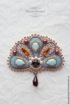 Handmade. Reminds me of a peacock, notice set stones sewn on instead of cabs.