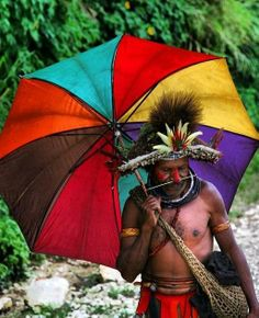 Colorful! A bright umbrella to keep the rain off this Huli man's bright headdress feathers.