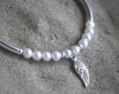 Angel wing bracelet silver sterling 925 moonstone, freshwater pearl and crystal quartz healing gemstones meaningful jewelry Angel wings      This bracelet measures 17.5 - 19.5 cms ( 6.9 inches - 7.7 inches ). With the use of the extension chain, this bracelet fits a range of wrist sizes comfortably. The 10mm little angel wing charm sits next to a hand forged sterling silver tube.      ❋ ❋ ❋ ❋ ❋ ❋ ❋ ❋ ❋ ❋ ❋ ❋ ❋ ❋ ❋ ❋ ❋ ❋ ❋ ❋      MOONSTONE    To calm and uplift.  Rainbow moonstone has a…