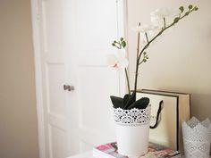 Ikea Skurar pot and orchid in neutral bedroom.