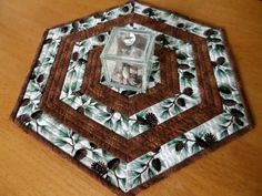 This pretty hexagon shaped holiday Christmas table topper can be used during the holiday season and during the winter months. You can also use this handmade quilted table mat as a candle mat.  Table topper features a beautiful metallic winter pinecones fabric and a coordinating brown print fabric (also used on the backing). Batting used is 100% cotton Warm and Natural brand. Quilting was done in parallel lines following the shape of the hexagon.  This listing is for the table topper only…