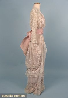 Hobble-style tea gown, circa 1913 (side.) One-piece dress fashioned from various laces including Val, torchon, and embroidered net. The skirt panels are embroidered with flower baskets. Wide pink brocade silk sash.