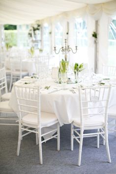 elegant tented wedding reception in all white | white chiavari chairs, white table cloths and napkins | trio of white floral centrepieces on top of round mirros and silver candelabras | A Springtime French Chateau Wedding