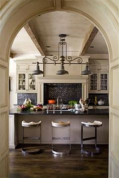 Paneled barrel arch entry into a great kitchen with a mantel style range hood.
